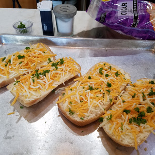 Sprinkle each slice with garlic powder and a pinch of kosher salt. Then lots of shredded cheese and a scattering of minced fresh parsley.