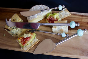 Various designs of cheese knives on a cheesboard.
