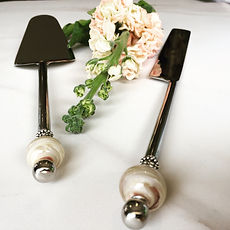 Stainless steel cake servers with glass bead handles.