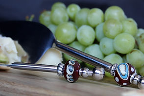 Close-up of cheese knives on a cheesboard with grapes.