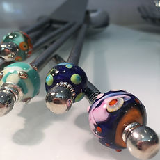 Close-up view of various beads on the shafts of stainless steel salad servers.