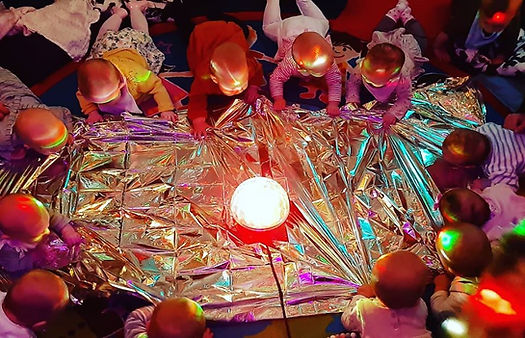 babies in a sensory class laying on their tummies with silver sheet and disco light.