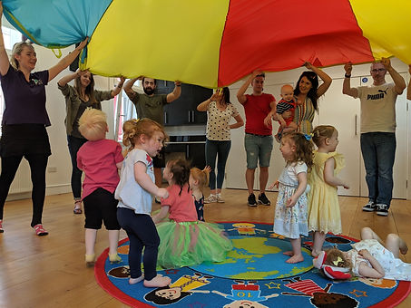 children laughing and playing under parachute with parents and carrie