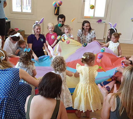 Easter party and disco parachute is being shaken with toy carrotts and eggs flying in the air