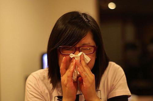 woman with sinus pain sneezing into kleenex