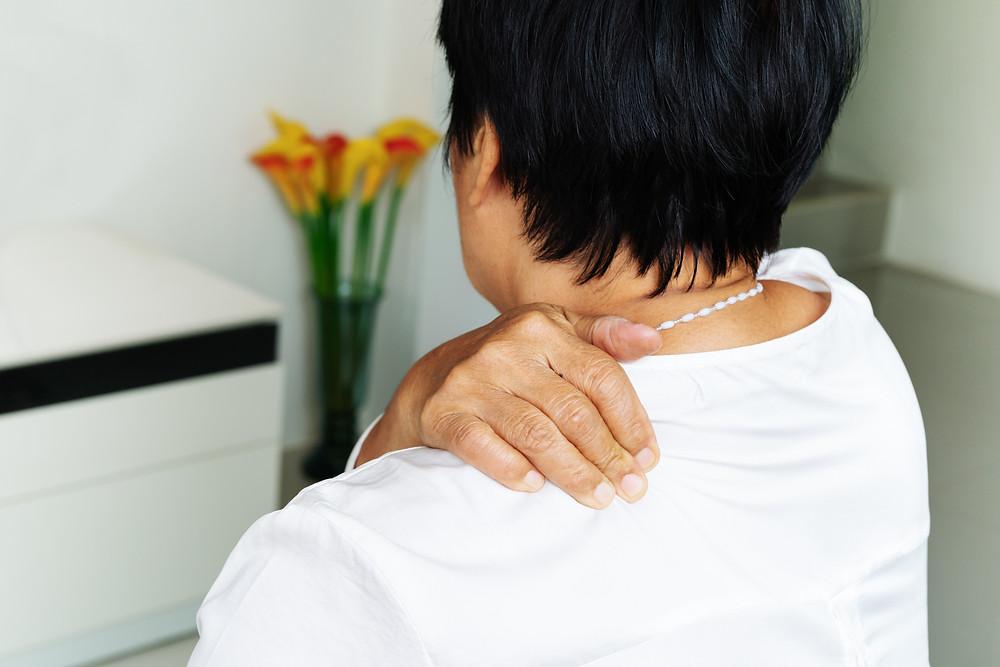 Person massaging pinched nerve in shoulder, neck area.