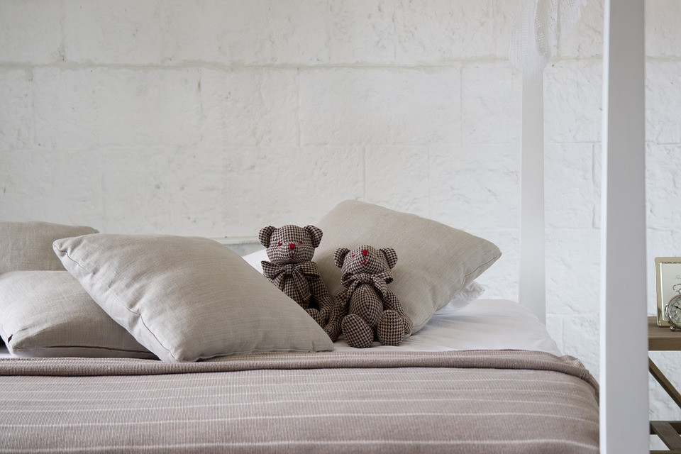 two teddy bears sitting on a bed
