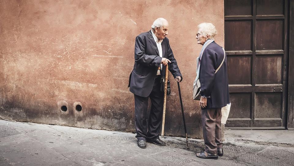 elderly couple talking outside on the sidewalk