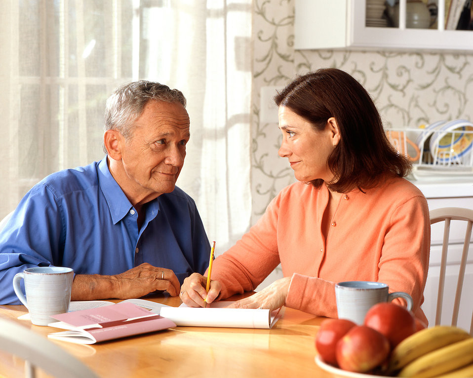 older couple together at table writing a list