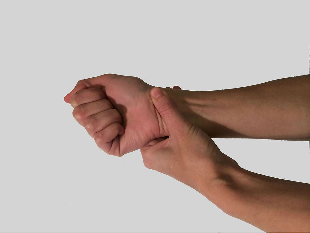 person holding wrist suffering from arthritis