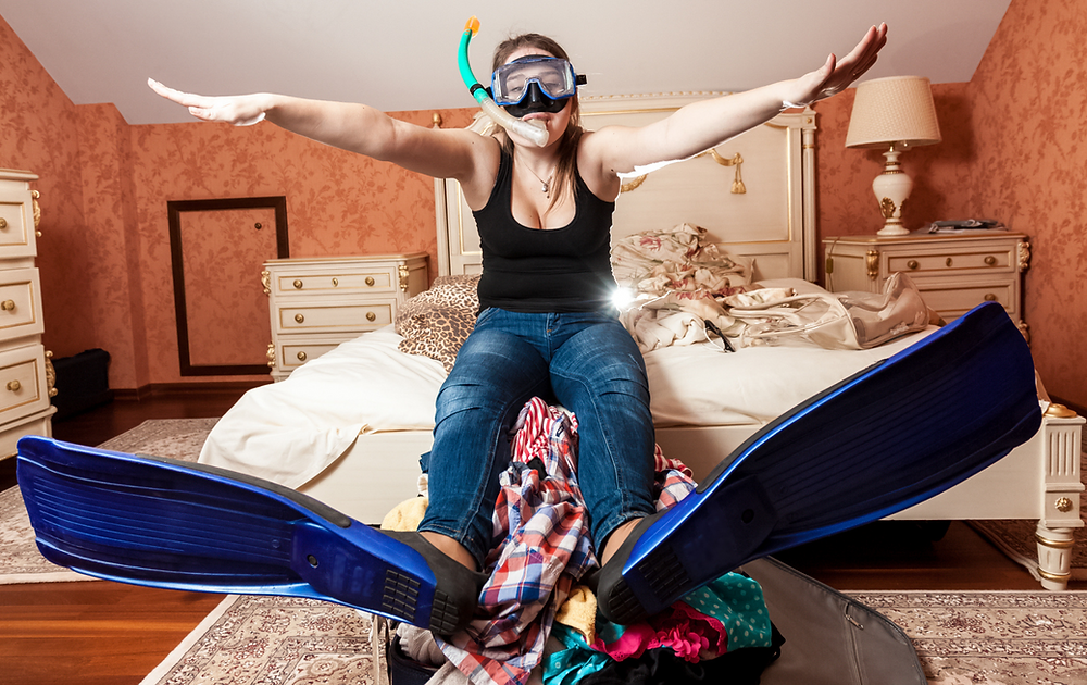 woman wearing snorkeling equipment sitting on edge of bed with legs on luggage and clothing pile
