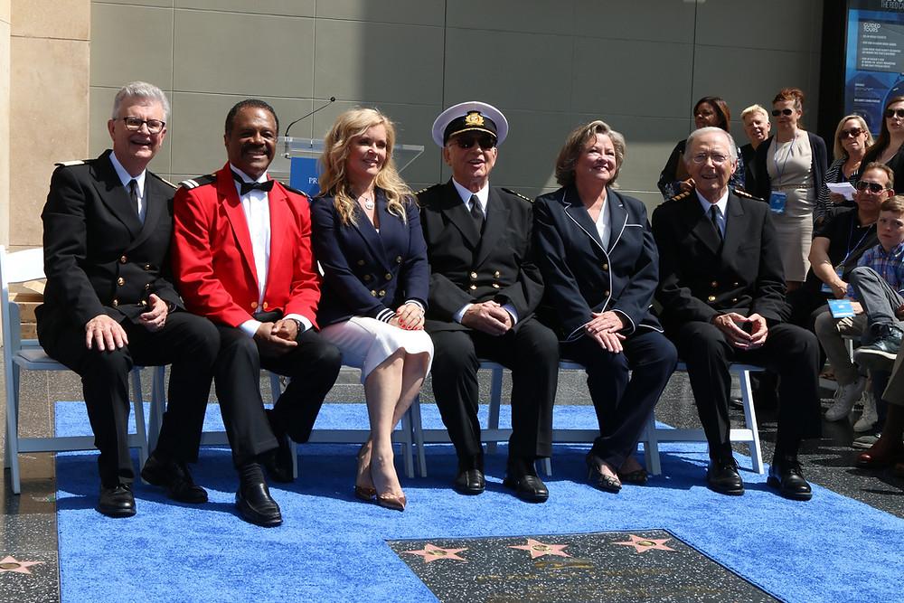 Fred Grandy, Ted Lange, Jill Whelan, Gavin MacLeod, Lauren Tewes, Bernie Kopell seated outside Doby Theater