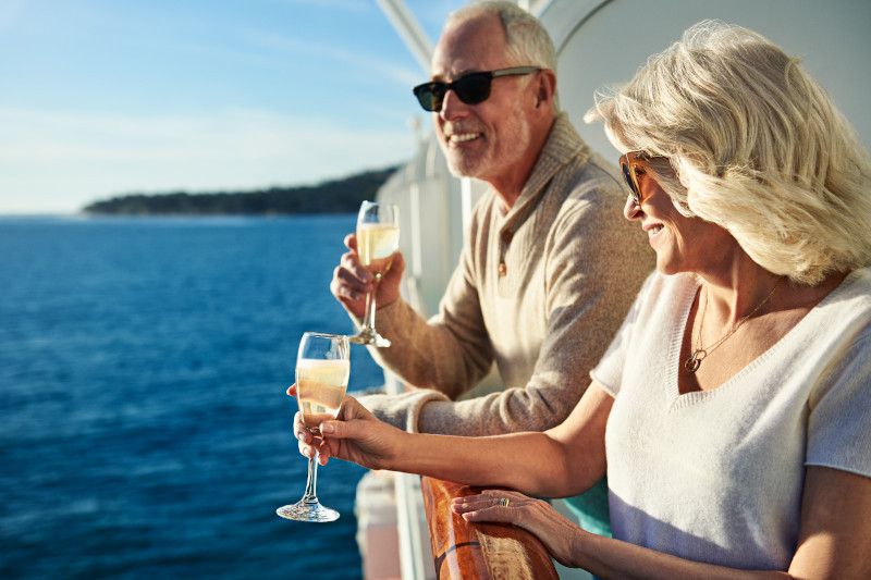 White couple leaning on a balcony railing holding champaige glasses