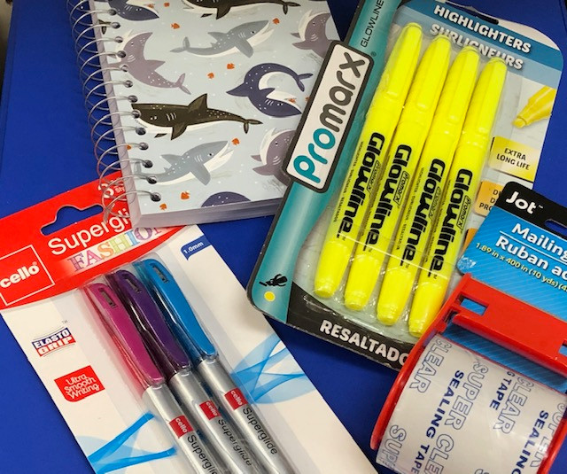 blue background with shark-covered spiral notebook, colored pens, yellow highlighters, shipping tape