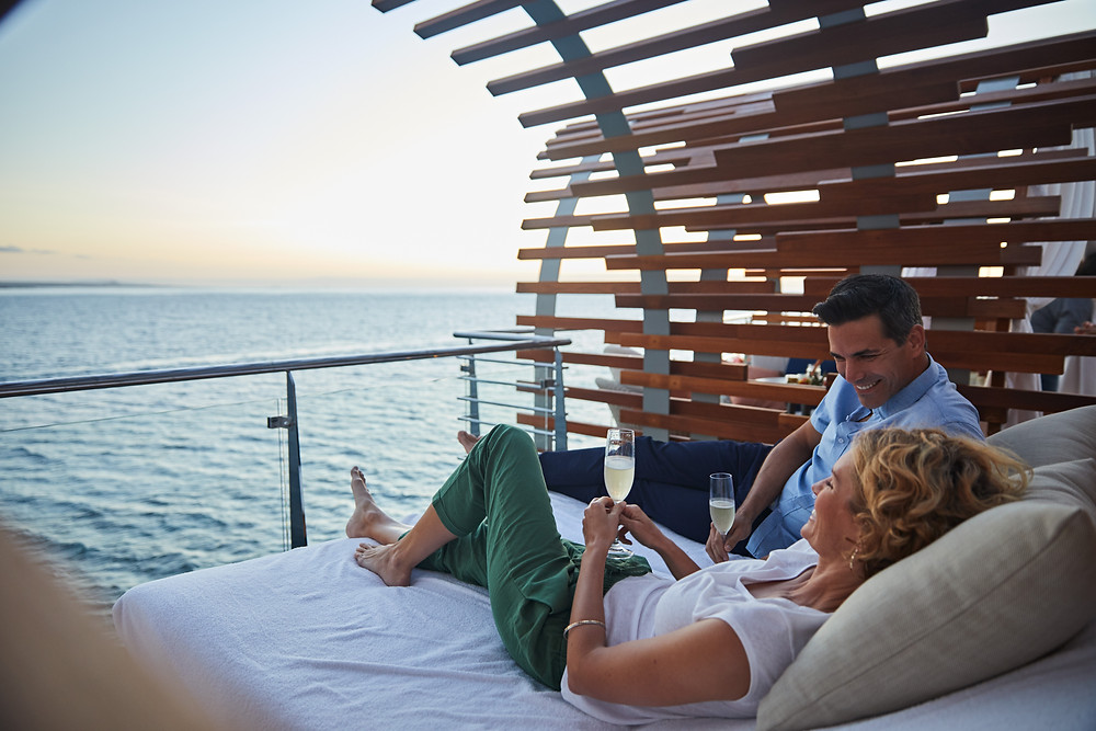 couple lounging on bed outdoor on cruise ship, overlooking water at sunset