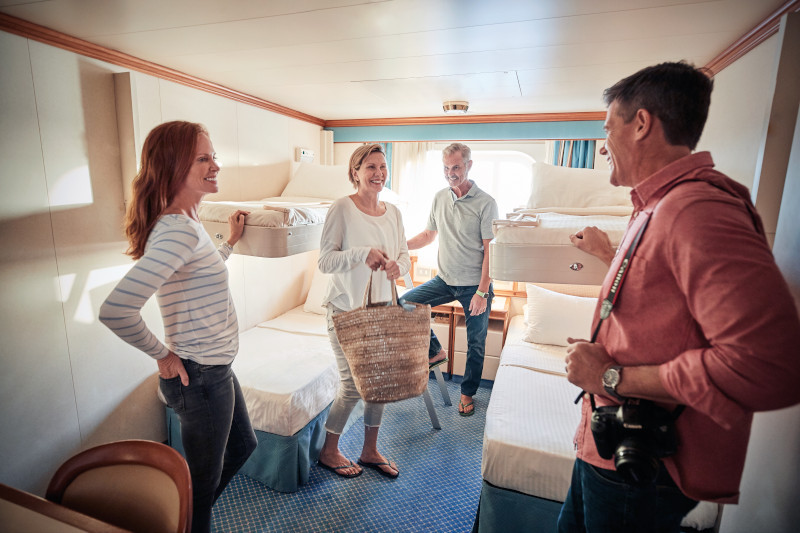 Four adults in a cruise cabin with two twin beds, blue carpet, window