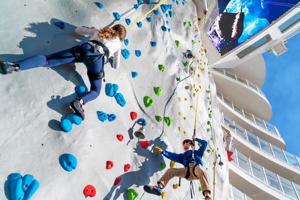 Two people climbing a rock climbing wall on a cruise ship