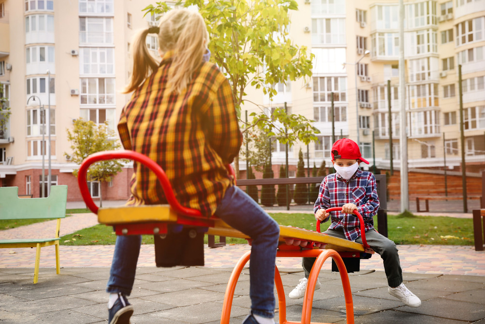 boy and girl playing on a yellow and red seesaw or teeter totter