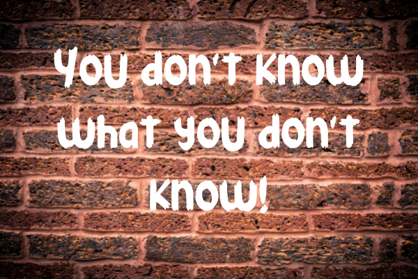 reddish brown brick wall with graffiti saying you don't know what you dont know