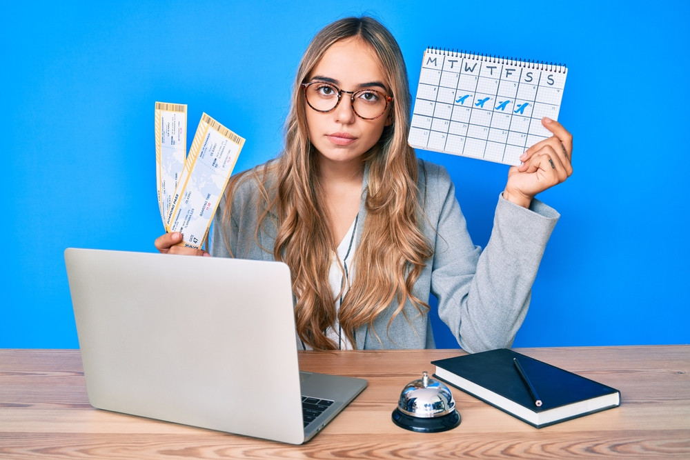 Young woman in front of a computer holding a calendar and airline boarding passes