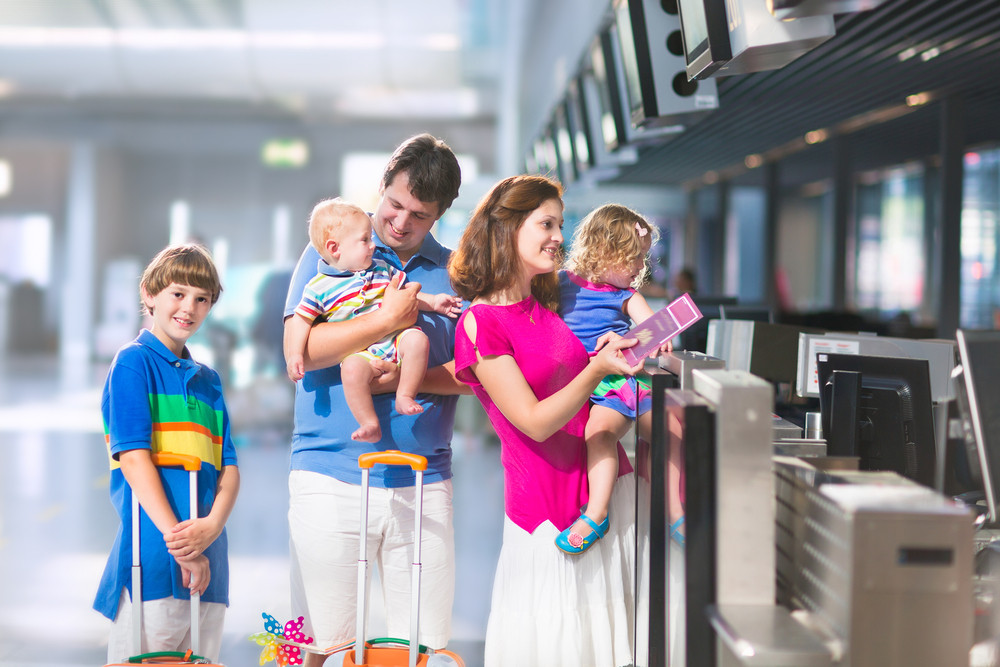 2 adults, child, toddler, baby checking in at airport with luggage