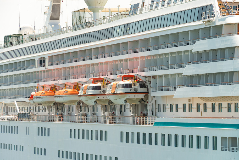 side of cruise ship with balconies, lifeboats and tender boats on the side
