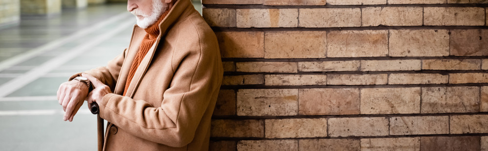 Elderly man in tan coat leaning against brick wall looking at his watch