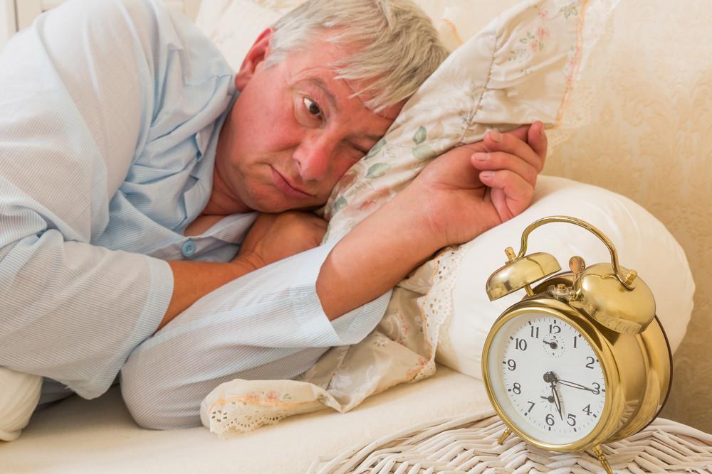 man in pajamas in bed staring at alarm clock