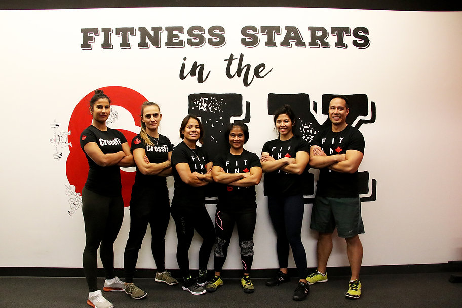 "Row of coaches at Fitness Fusebox posing in front of a wall mural reading, ""Fitness Starts in the 6IX"""