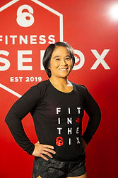 Emie Ocampo, kickboxing coach of Fitness Fusebox, stading in front of a wall bearing the Fitness Fusebox logo