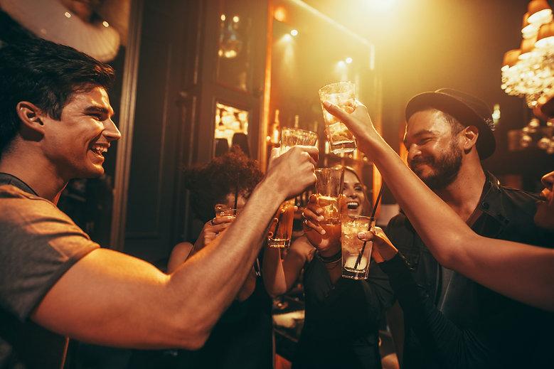Freunde trinken in einer Bar, stoßen an und haben Spaß