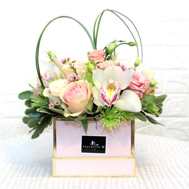arrangement de fleurs dans une boîte à chapeau