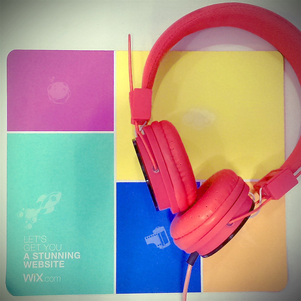 Red headphones on colorful mouse pad
