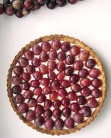 Vegan hazelnut tart with vanilla cream and red grapes.