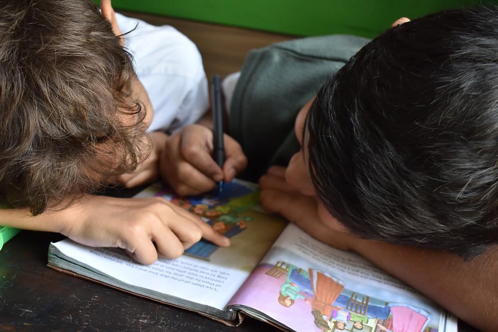 Kinder malen in einem Buch