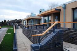 grey brickwork with wooden handrail