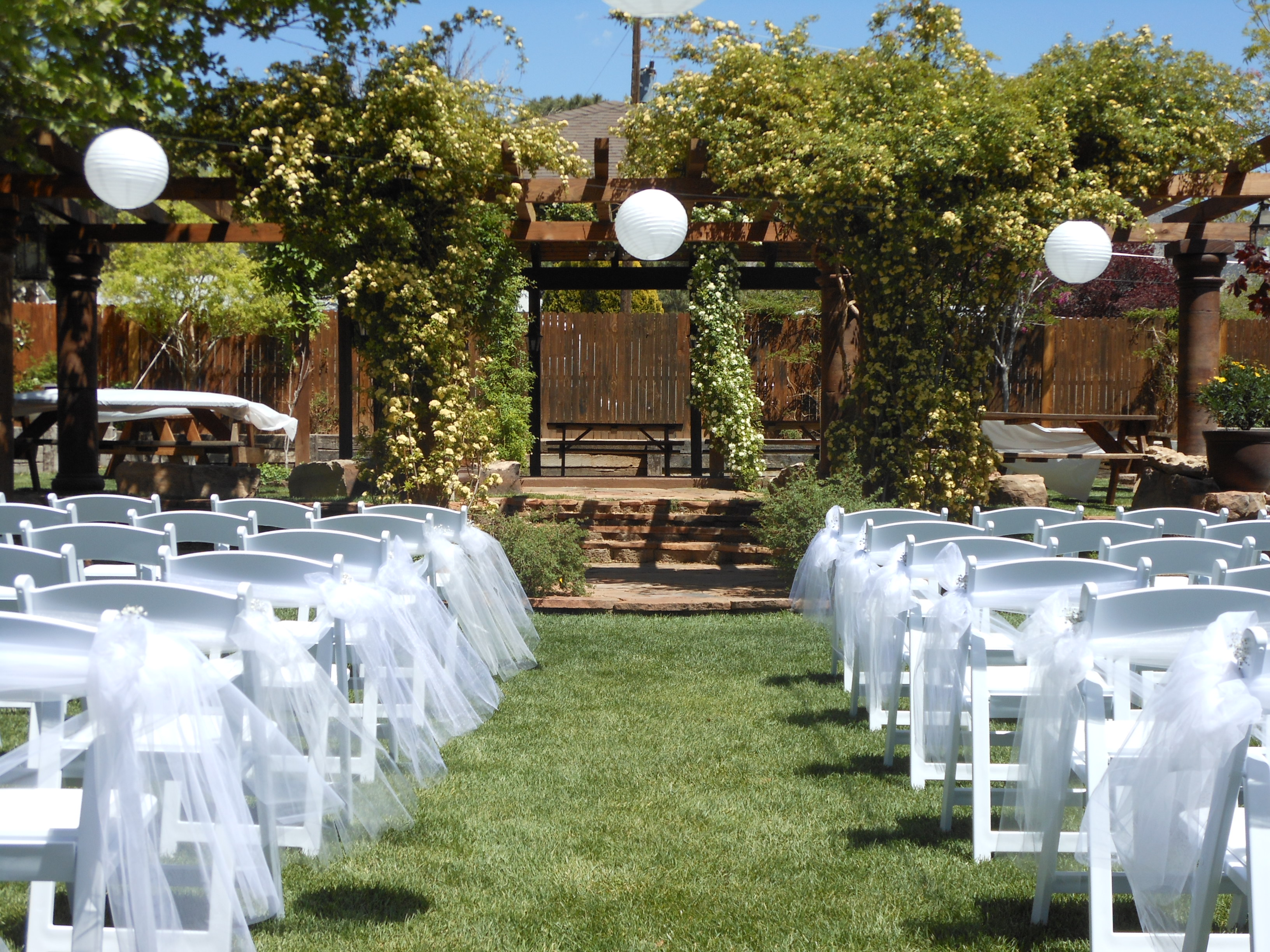 chairs with tulle and arbor facing East