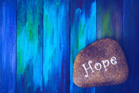 words  _Hope_ painted on river stone ove