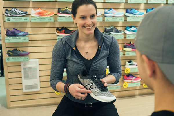 Photo of Sole Train's owner and pedorthist, Laura Mazier, showcasing footwear to a client.