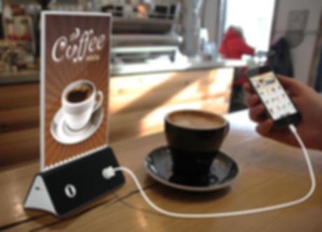 Una estacion de carga cargargo un celular y una taza de café a un lado