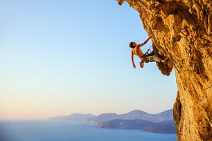 Young man looking up while climbing chal