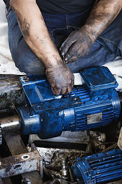 Hand of repairman holding hexagonal wrench and during maintenance work of electric motor
