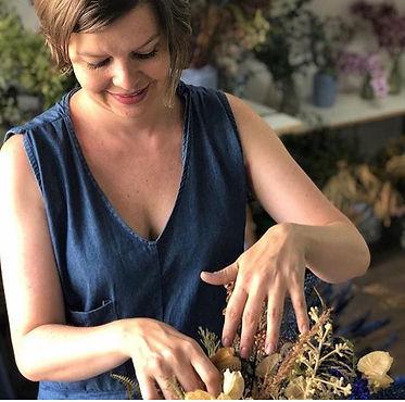 Roberta Tassinari mexenda em um arranjo de flor