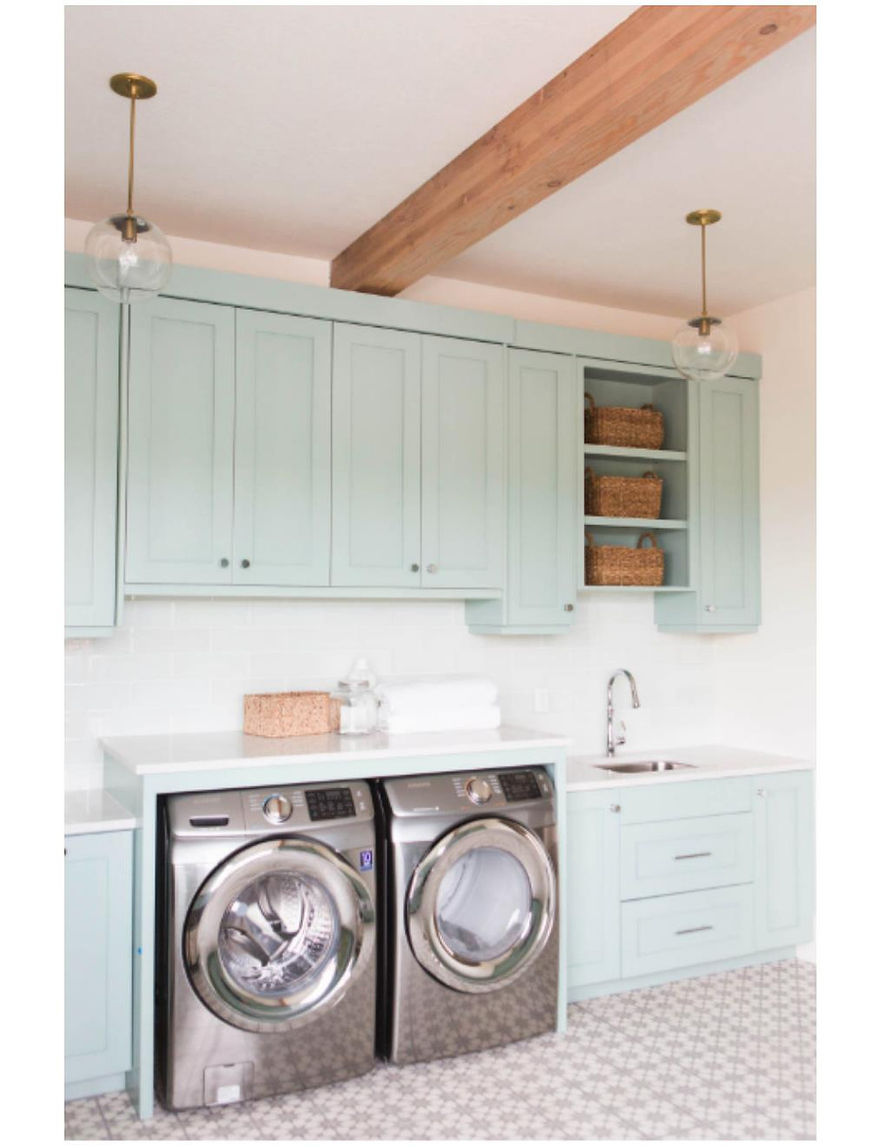 teal laundry room with counter above washer and dryer
