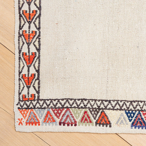 Hand woven natural wool kilim with hand embroidered wool border