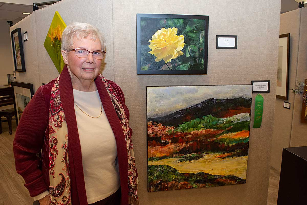 Image of Katey Sandy with her 3rd place painting Walk In The Wilderness