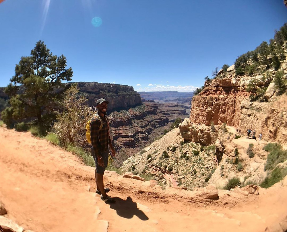 Antwan Johnson, outdoor enthusiast, standing near the edge of the Grand Canyon, smiling.
