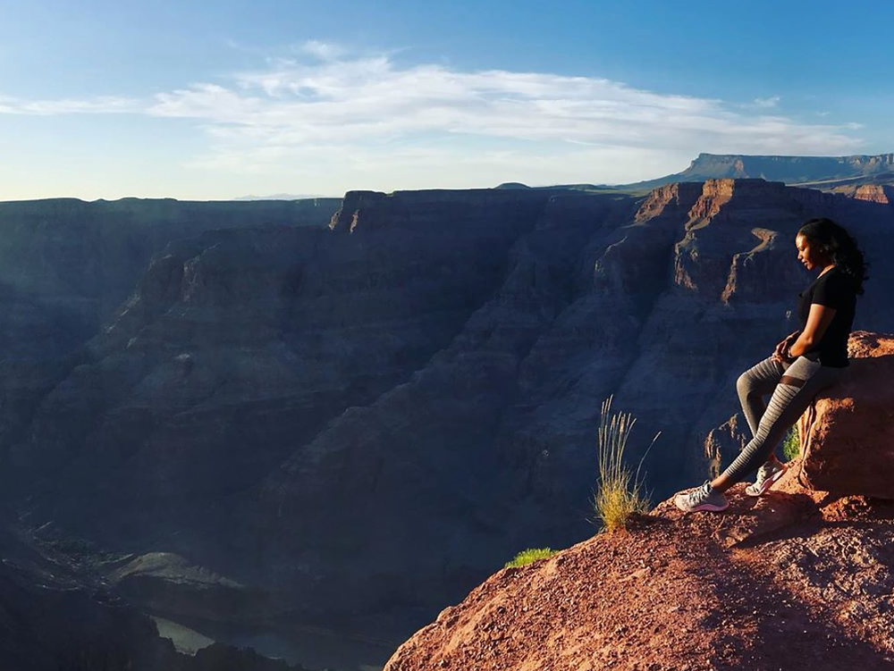 Karena Gill, PhD student, sitting on a rock while looking down into the Grand Canyon.