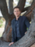 Photo of Neil Spark, waist up, beween tree branches.