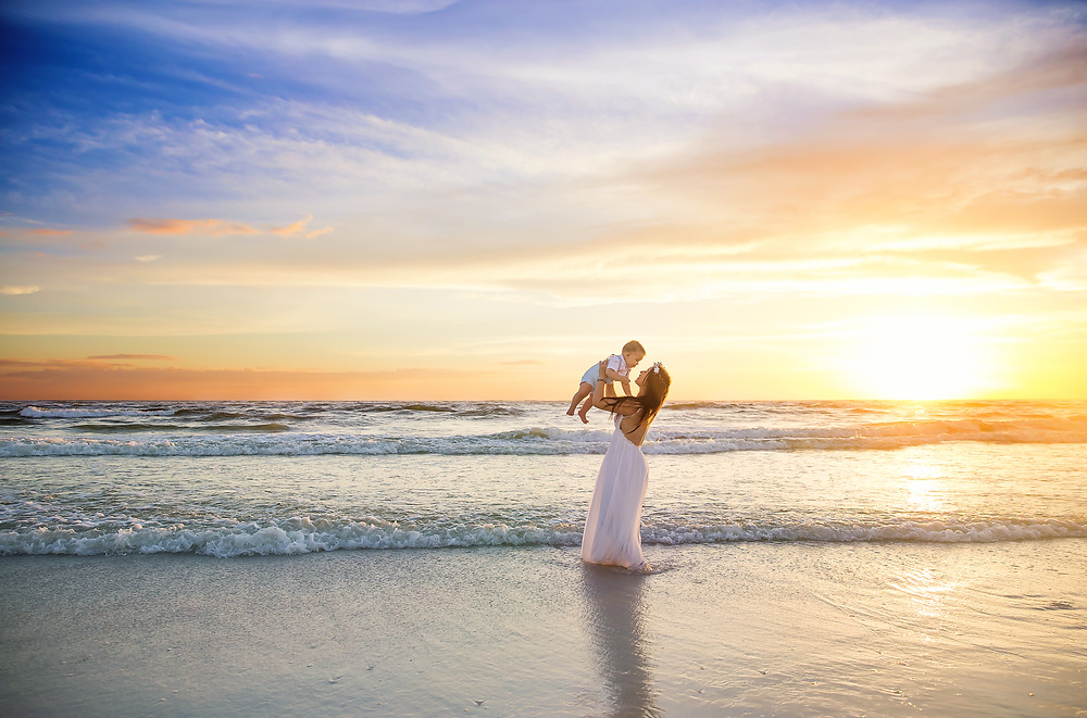 Mommy and son with a beautiful sunset during beach photo shoot